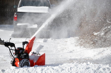 snow blower blowing snow away from driveway Stock Photo