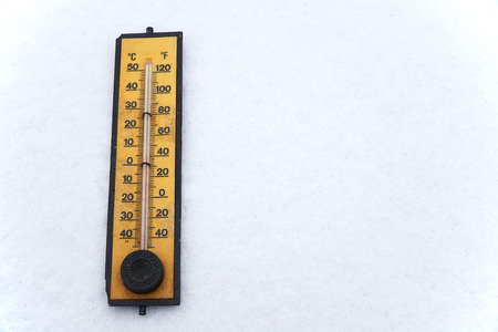old thermometer on white snow background