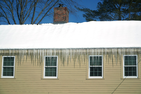 accumulated snow on roof with icicle hanging at roof edge
