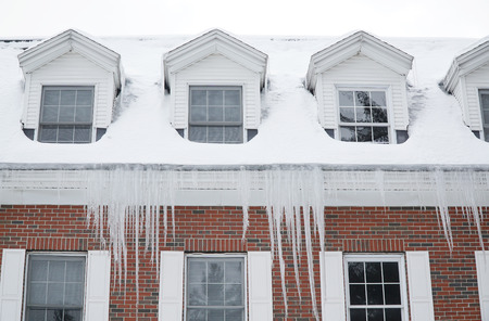 close up on old apartment building roof after snow with icicle
