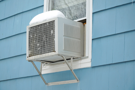old air conditioner installed on house window after winter snow Banco de Imagens