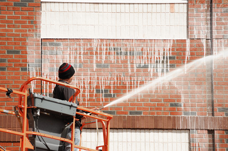 outdoor worker cleaning the exterior wall of building through pressure water Banco de Imagens