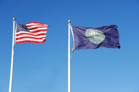 New Hampshire state flag and USA national flag waving under blue sky Stock Photo