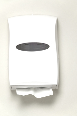 automatic paper towel dispenser mounted on the wall of bathroom Фото со стока