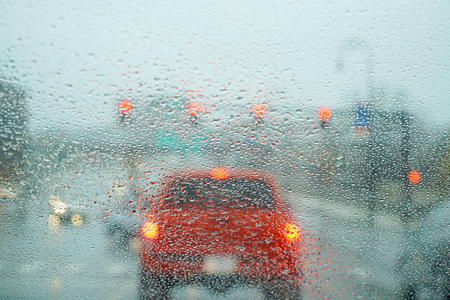 blurred street scene through car windows with rain drop Stock Photo
