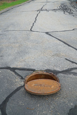 close up on opened rustic manhole cover on the street Stock Photo