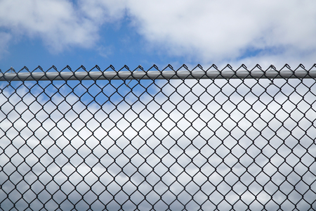 iron chain link fence against sky Banco de Imagens
