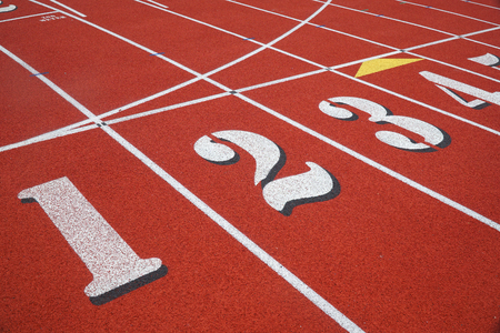 red running track in sport field with multiple lanes
