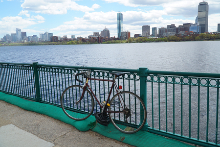 single bicycle in front of railing on the bank of Charles river in Boston
