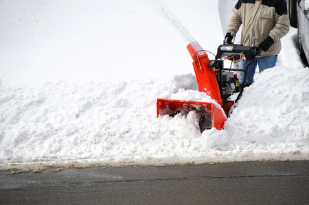 man operating snow blower to remove snow on driveway Standard-Bild