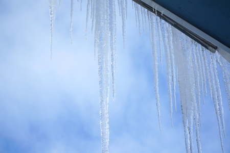 Close up on icicle hanging on the house roof Stock Photo