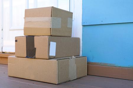 ドアの前に置かれる配達された積み重ねパッケージ 写真素材