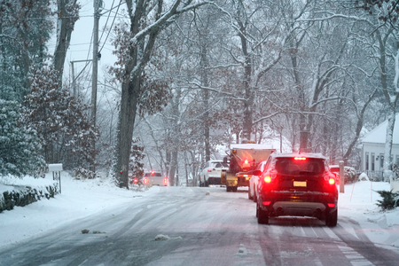 Vehicles stopping on the road after snow in residential area