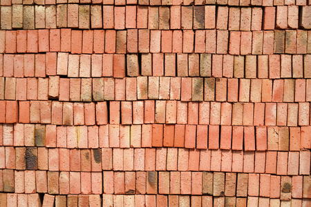 stacking red bricks as construction material background Imagens