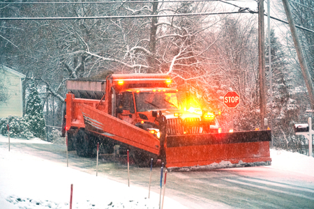 snowplow truck removing snow in the street in the storm Stock Photo