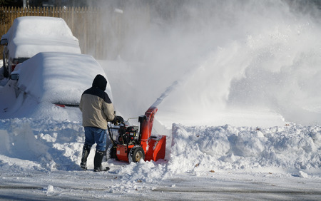 Man removing snow on the driveway of the house by snow blower Stock Photo