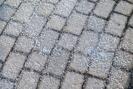 Melting salt on the sidewalk in winter season Stock Photo