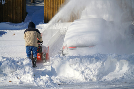 man removing snow on the driveway of the house by snow blower