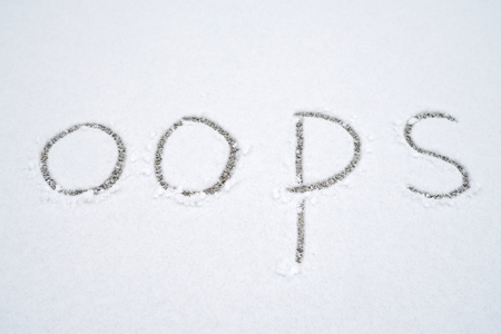 Hand written Oops sign on white snow background