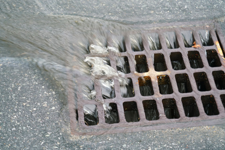 Close up on rain water flowing into manhole on the street