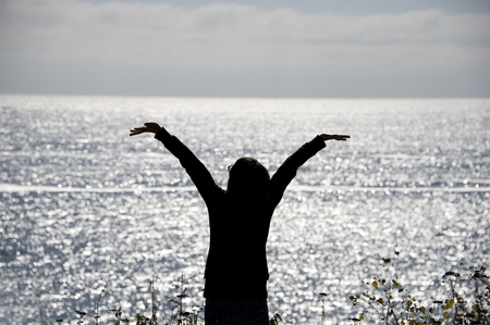 silhouette of cheering woman in front of the sea Stock Photo
