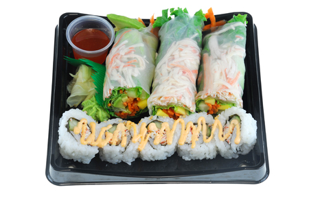 close up on fresh spring roll and sushi on black tray