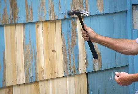 handyman repairing the house wall with hammer