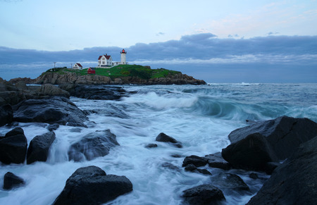 nubble lighthouse with rock beach in twilight