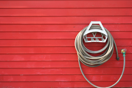 background of garden hose reel mounted on the wall