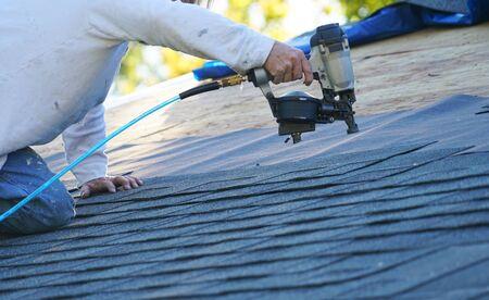 Manitas con pistola de clavos para instalar tejas para reparar el techo Foto de archivo