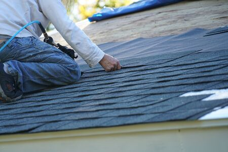 worker install new shingle on the roof of the house for roof repair Stock Photo