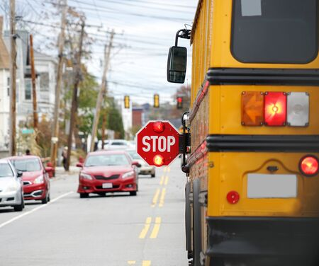 school bus with stop sign flashing on the street Imagens