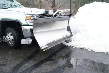 LKW mit Schneepflug vor Schneehaufen