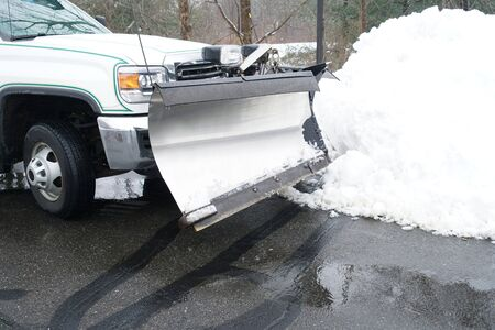 truck with snowplow in front of snow pile