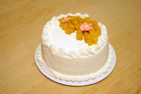 close up on fresh birthday cake with frosting cream and mango