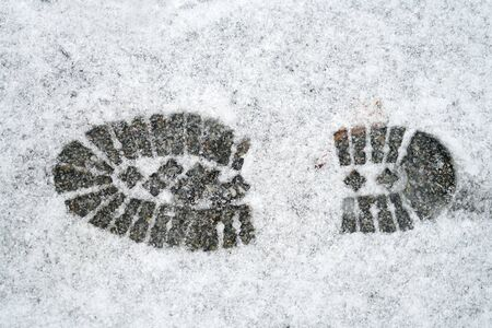 single boot footprint on the white snow