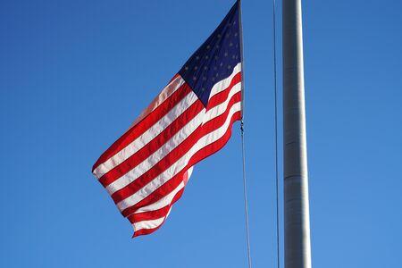 waving USA flag on pole against blue sky 版權商用圖片