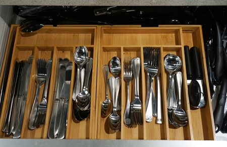 close up on forks and spoons in the tray in drawers