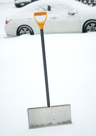 close upon snow shovel in snow and vehicle as background