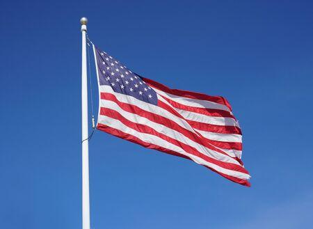 waving USA flag on pole against blue sky