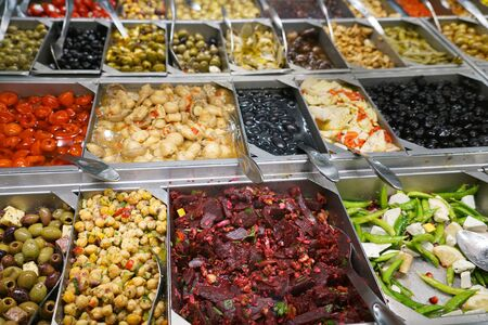 variety of colorful fresh vegetable salad in container in restaurant