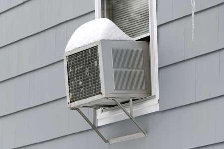 old air conditioner installed on house window with snow on top Stok Fotoğraf