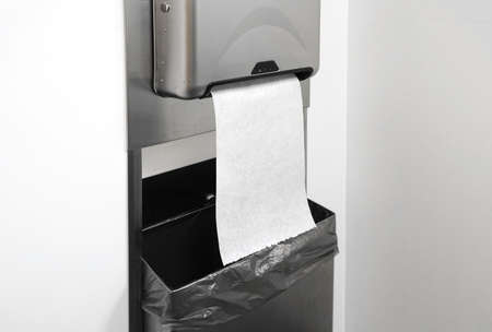 close up on paper towel dispenser on the wall