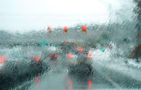 landscape of urban street in the rain through car window