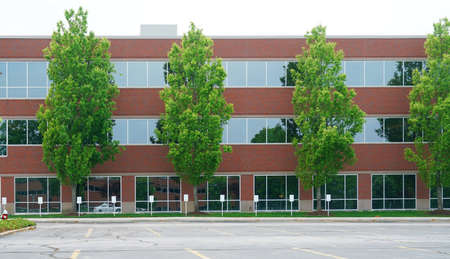 facade view of office building with green trees in front Stok Fotoğraf