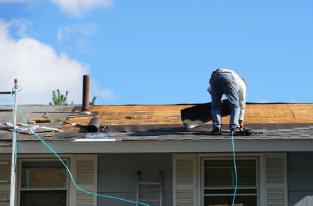 worker install new shingle on the roof of the house for roof repair Stok Fotoğraf