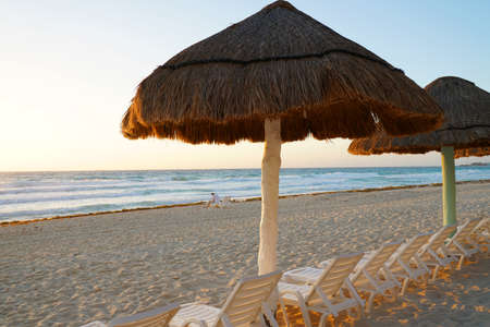 thatch umbrella in the beach under morning sunlight Stok Fotoğraf