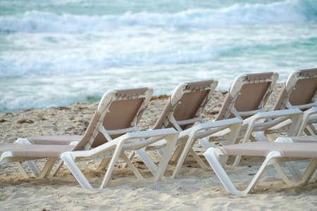 beach deckchairs in a row in the beach
