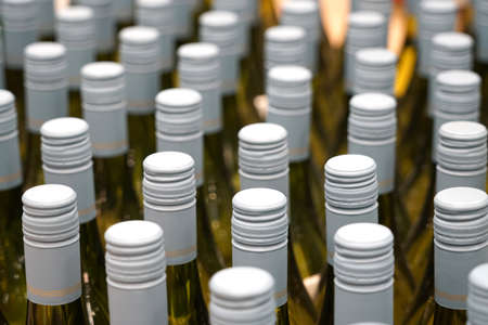close up on white wine bottles in rows