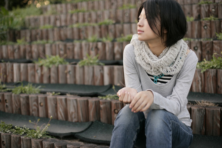 Young woman sitting outside LANG_EVOIMAGES